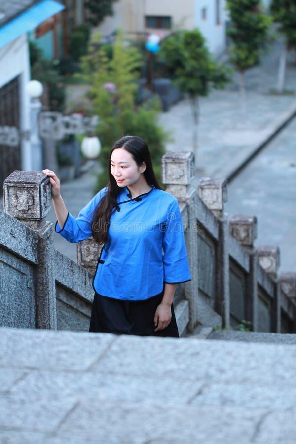 Donna cinese asiatica nel vestito tradizionale dello studente in Repubblica Cinese al muro di cinta antico di Dali fotografie stock