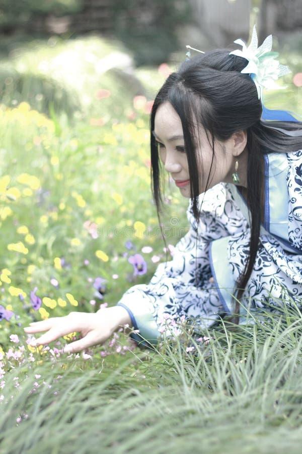 Donna cinese asiatica in vestito blu e bianco tradizionale da Hanfu, gioco in un giardino famoso, stante fra i fiori fotografie stock
