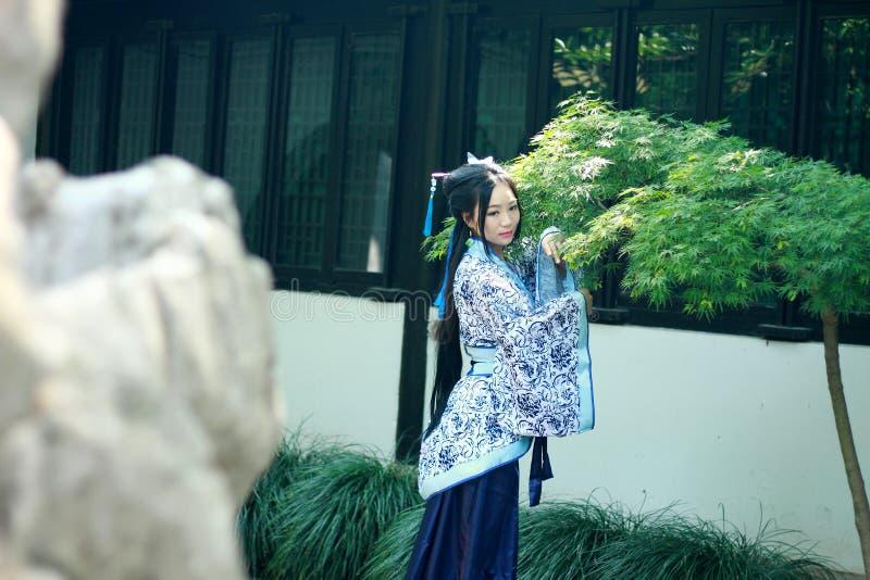 Donna cinese asiatica in vestito blu e bianco tradizionale da Hanfu, gioco in un giardino famoso vicino alle finestre fotografia stock libera da diritti