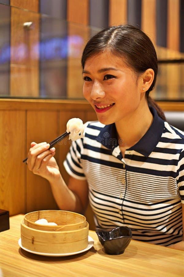 Donna cinese che mangia gnocco cotto a vapore in ristorante fotografia stock
