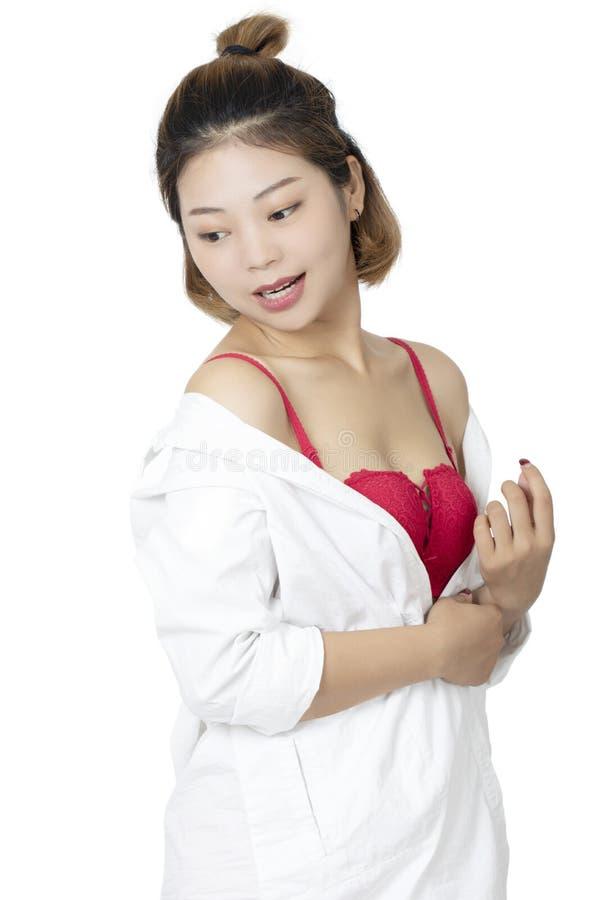 Donna cinese che posa in camicia bianca su fondo bianco immagini stock