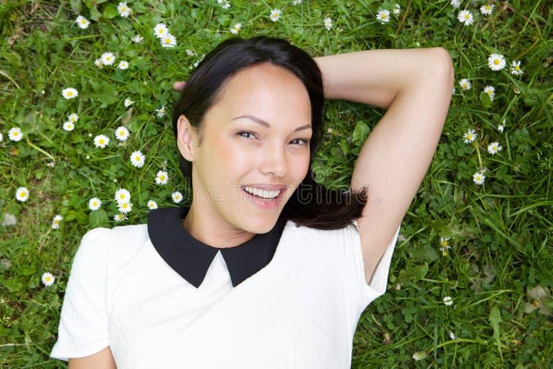 Donna cinese che si trova sull'erba e sul sorridere immagini stock