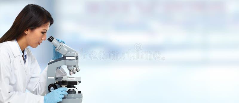 Donna cinese di medico con il microscopio fotografia stock