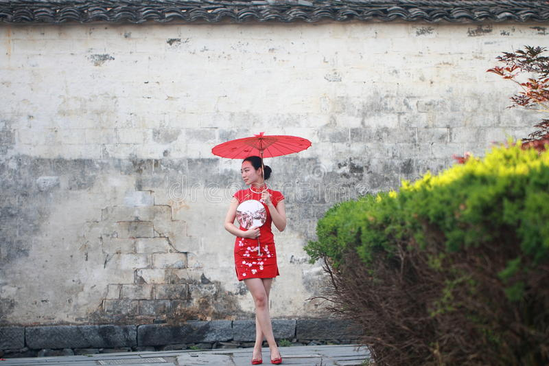 Donna cinese felice nel giro rosso del cheongsam alla città antica fotografie stock
