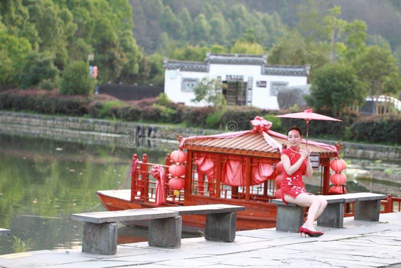 Donna cinese felice nel giro rosso del cheongsam alla città antica fotografia stock