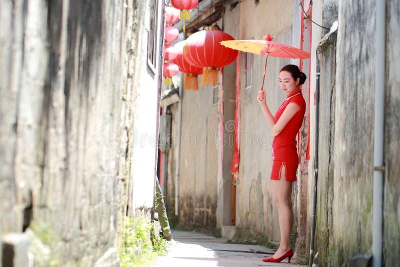 Donna cinese felice nella passeggiata rossa del cheongsam nel vicolo immagine stock