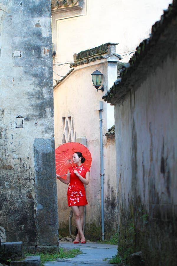 Donna cinese spensierata nel cheongsam rosso che beve e colta fotografie stock libere da diritti