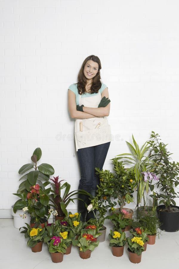 Donna circondata dalle varie piante in vaso fotografia stock libera da diritti
