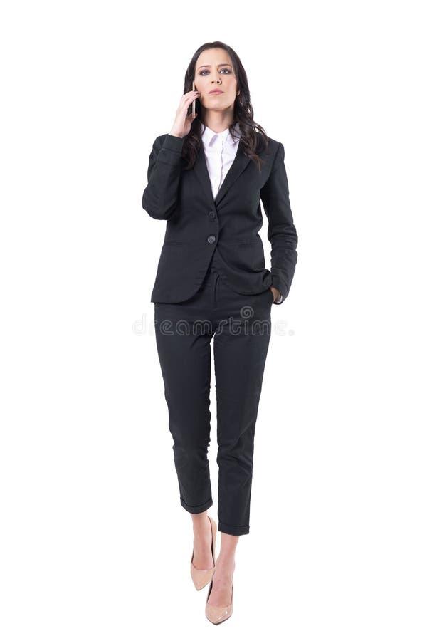 Donna comandone di affari di atteggiamento serio che parla sul telefono cellulare che cammina verso la macchina fotografica immagine stock