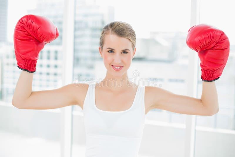 Donna competitiva sorridente con i guantoni da pugile rossi che incoraggia su immagini stock libere da diritti