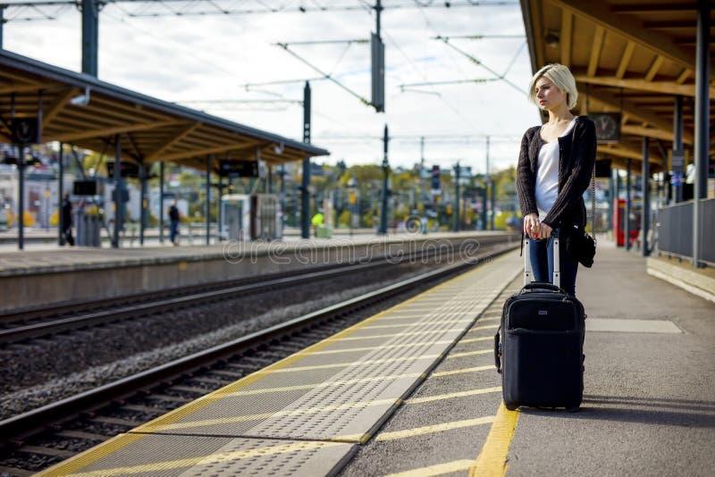 Donna con bagagli che aspettano sul binario della stazione ferroviaria fotografie stock libere da diritti
