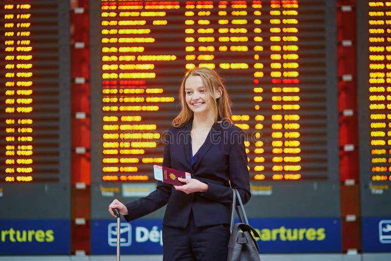 Donna con bagaglio a mano in terminale di aeroporto internazionale, esaminante il bordo di informazioni fotografia stock
