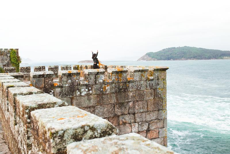 Donna con a braccia aperte dentro una fortezza sul mare immagini stock