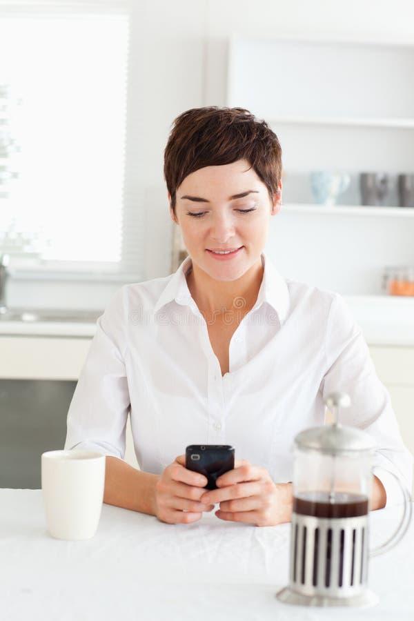 Donna con caffè che osserva al suo telefono mobile fotografia stock libera da diritti