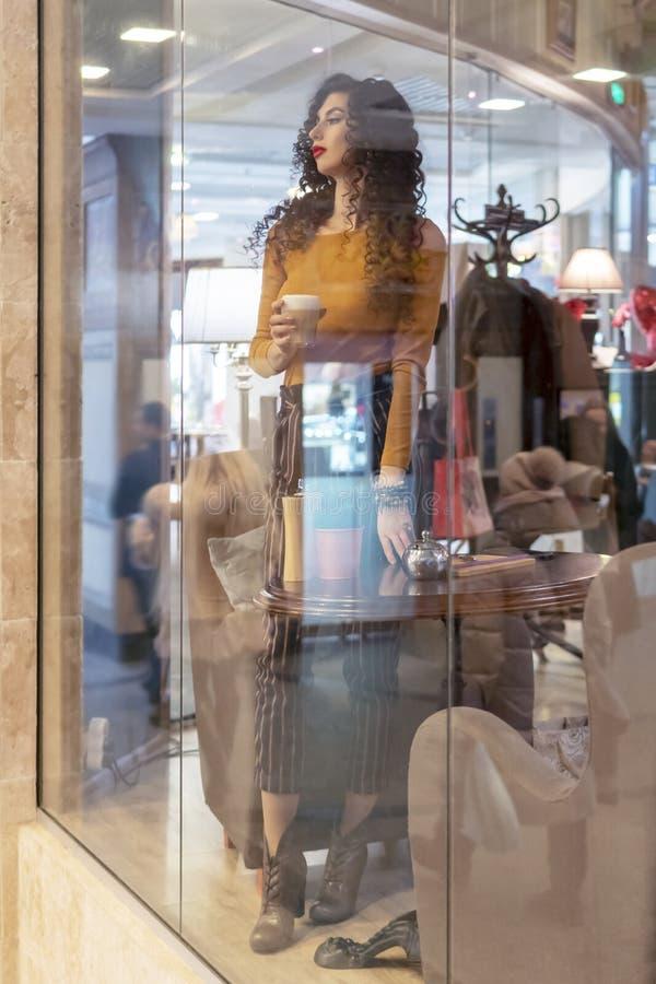 Donna con caffè dietro vetro fotografie stock