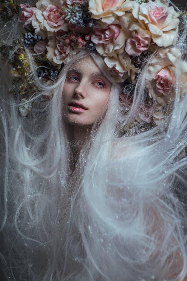 Donna con capelli bianchi e rose bianche e neve fotografia stock libera da diritti