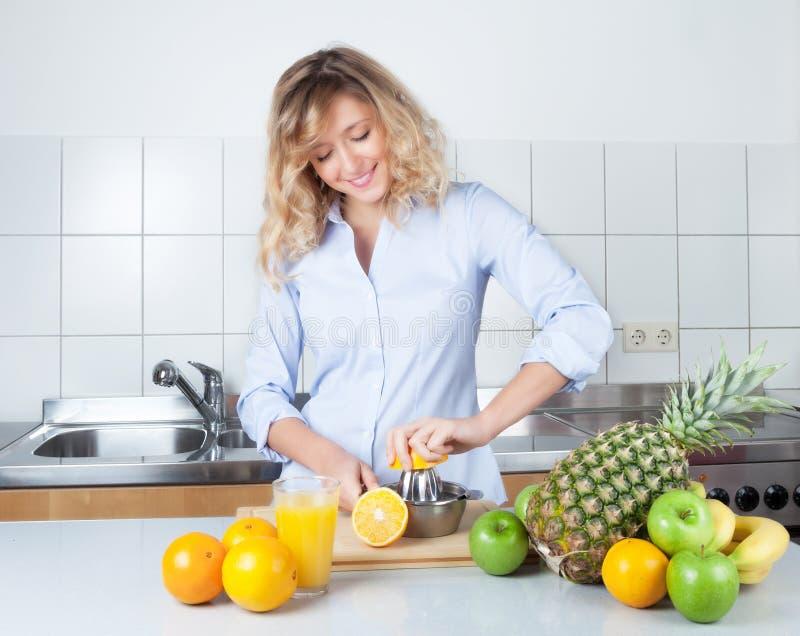 Donna con capelli biondi ricci che preparano il succo di orango nella cucina immagini stock libere da diritti
