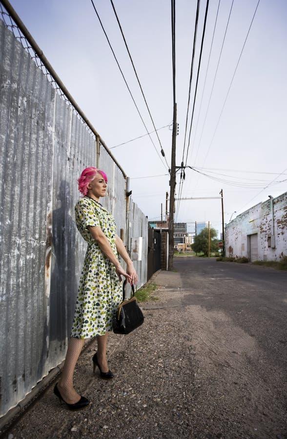 Donna con capelli dentellare e una borsa in un vicolo fotografie stock libere da diritti
