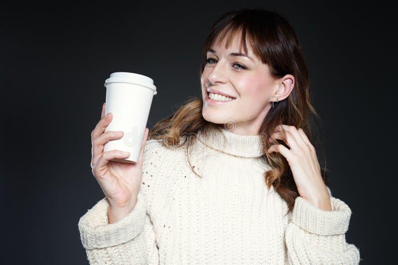 Donna con capelli lunghi con la tazza di caffè eliminabile asportabile in mani, maglione bianco d'uso di inverno, fondo grigio sc fotografie stock libere da diritti