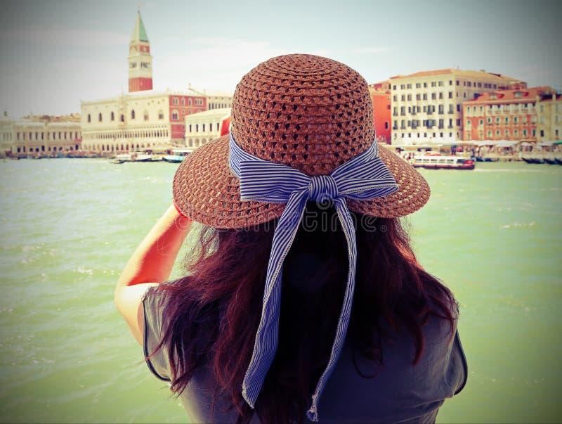 Donna con capelli marroni e un cappello di paglia ed il grande campanile i fotografie stock