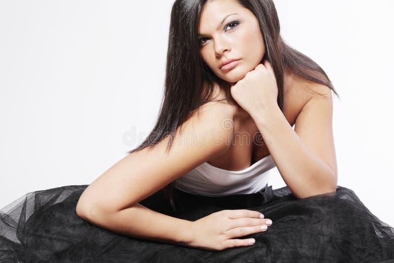 Donna con capelli neri lunghi su priorità bassa bianca. fotografia stock