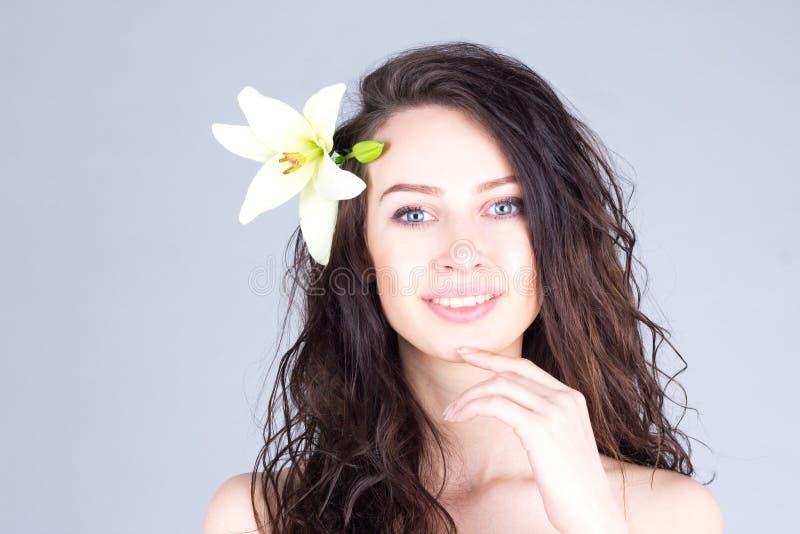 Donna con capelli ricci ed il giglio in capelli che sorridono con i denti ed il mento commovente Umore hawaiano immagine stock