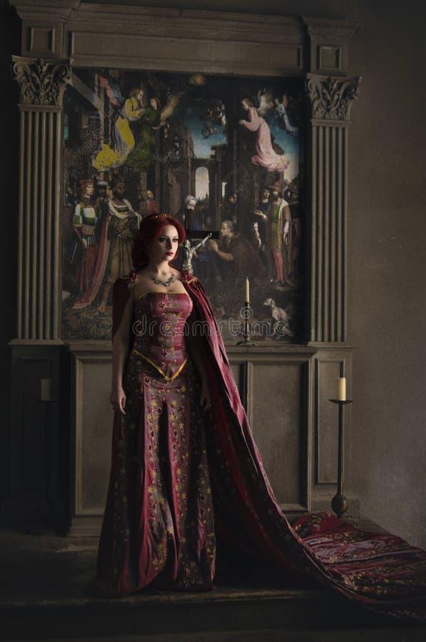 Donna con capelli rossi che indossano abito reale elegante immagine stock