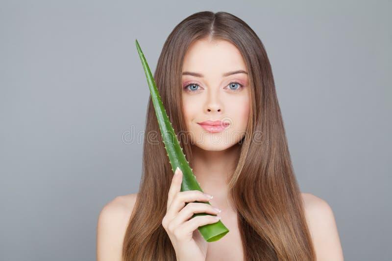 Donna con capelli sani lunghi che tengono la foglia verde dell'aloe fotografie stock libere da diritti