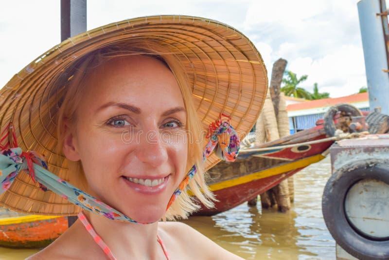 Donna con cappello tradizionale vietnamita seduta sulla barca fotografia stock libera da diritti