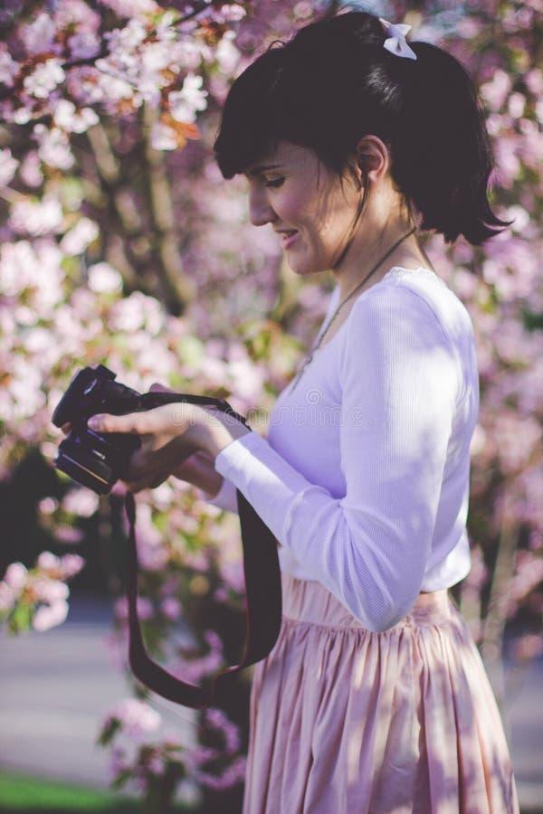 Donna con cintura di sicurezza esterna in bianco con gonna lunga superiore e gonna rosa con telecamera Dsler nera fotografia stock libera da diritti