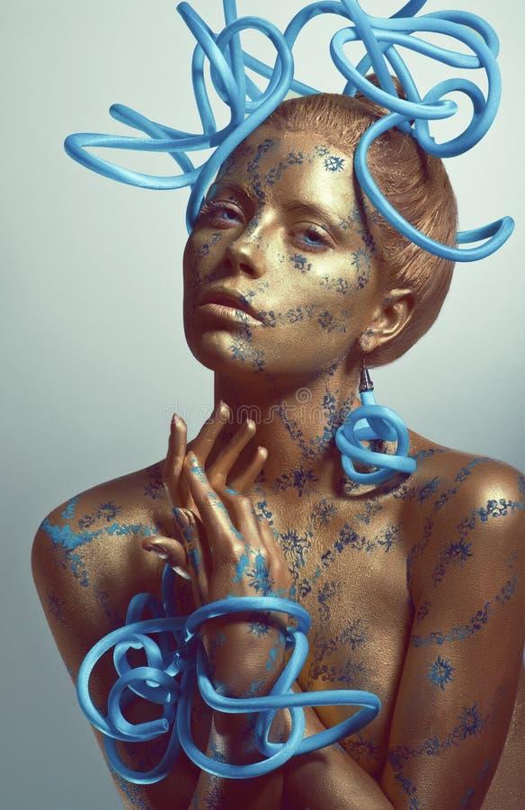 Donna con corpo-arte dorata ed i tubi blu fotografia stock