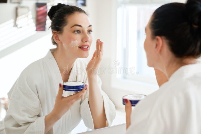 Donna con crema per il suo fronte fotografie stock libere da diritti