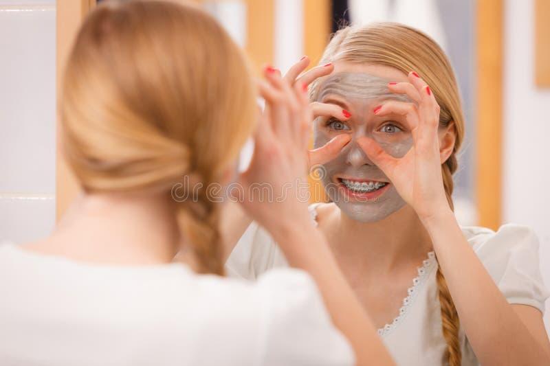 Donna con divertiresi della maschera del fango dell'argilla immagine stock
