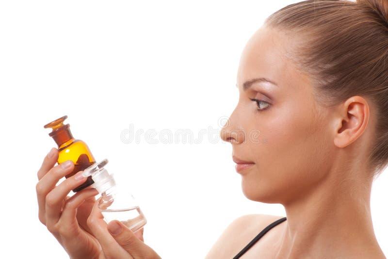 Donna con due bottiglie di medicina o di profumo fotografia stock libera da diritti