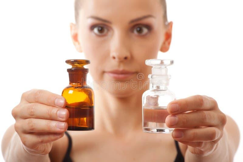 Donna con due bottiglie di medicina o di profumo immagine stock libera da diritti