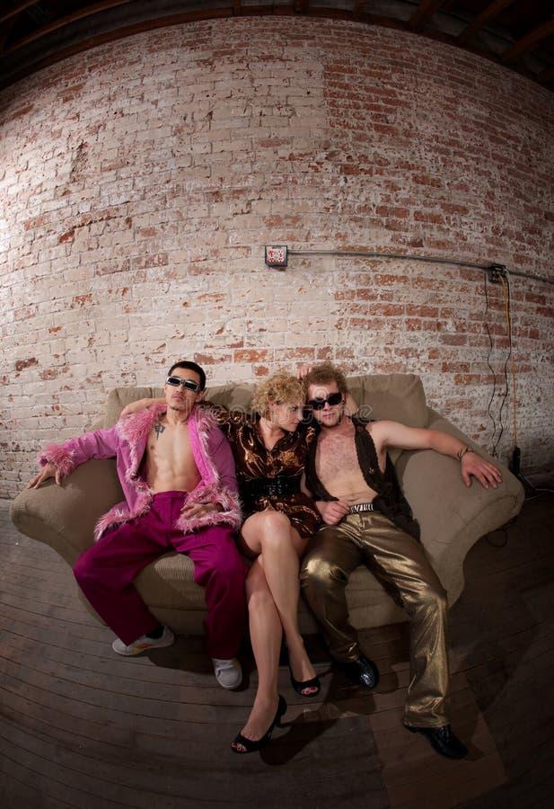 Donna con due tiranti freddi che si siedono su un sofà immagini stock libere da diritti