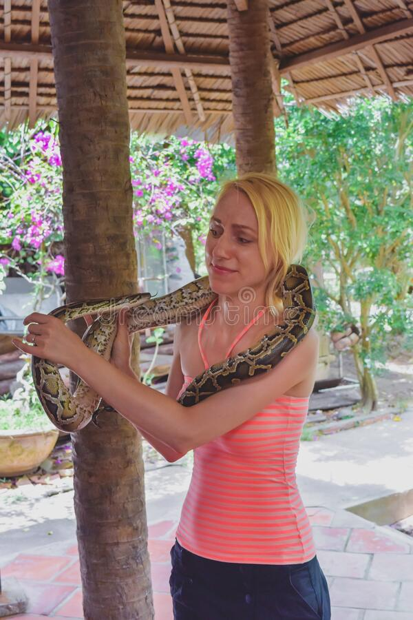 Donna con faccia spaventosa che tiene in mano un serpente immagine stock libera da diritti