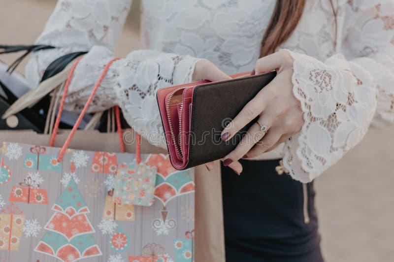 Donna con gli acquisti che tengono una borsa di cuoio fotografia stock