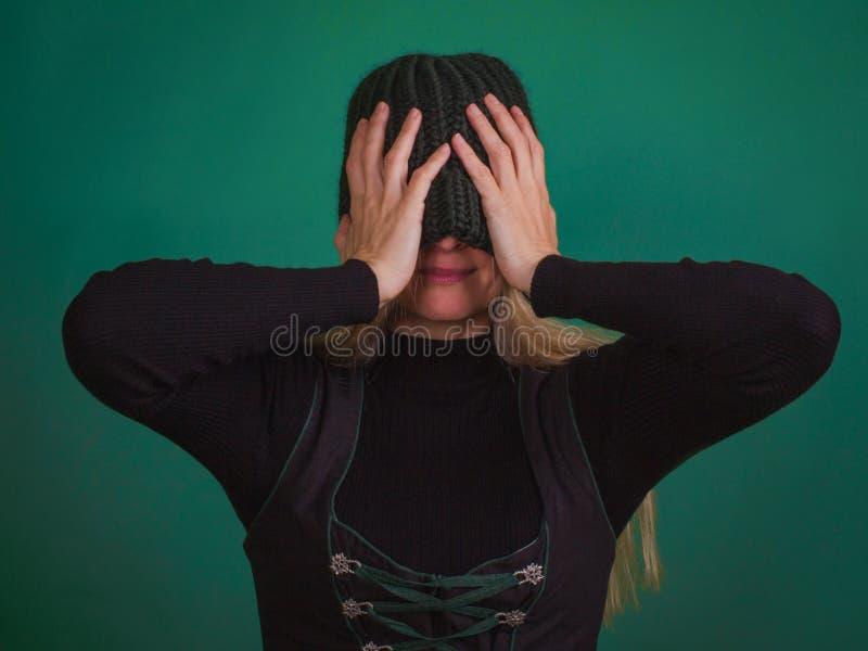 Donna con gli occhi alla moda tricottati della copertura del cappello fotografia stock