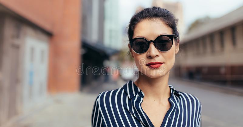 Donna con gli occhiali da sole che cammina all'aperto sulla via della città fotografia stock libera da diritti
