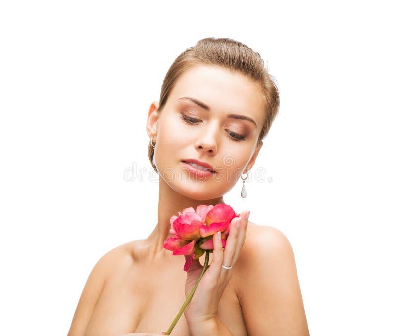 Donna con gli orecchini, l'anello ed il fiore del diamante immagine stock libera da diritti