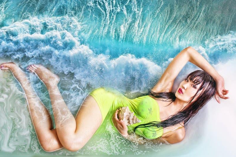 Donna con i capelli del browm e le gambe lunghe che si trovano nell'acqua fotografia stock