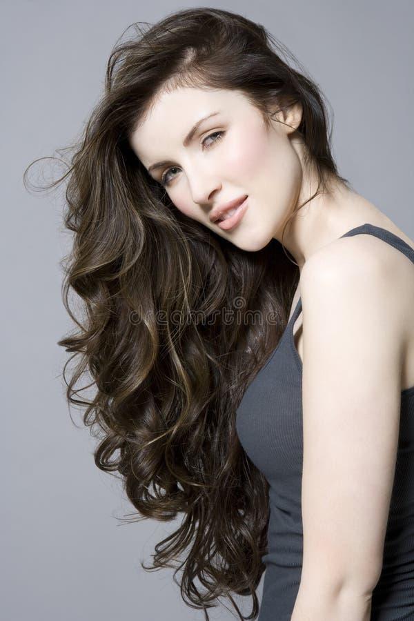 Donna con i capelli ondulati lunghi di Brown fotografia stock libera da diritti