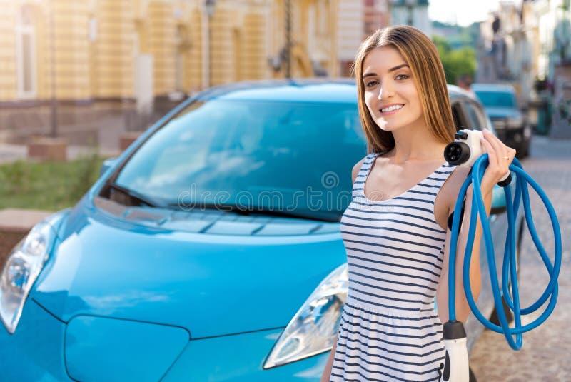 Donna con i cavi davanti all'automobile immagini stock libere da diritti