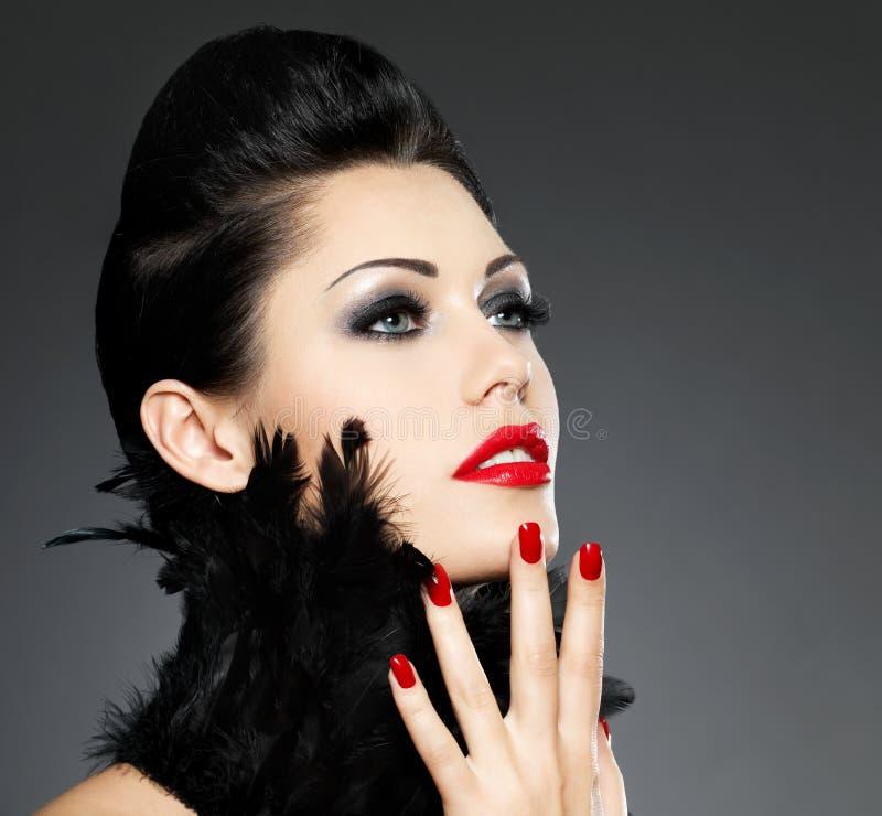 Donna con i chiodi rossi e l acconciatura creativa