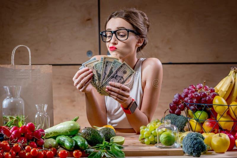 Donna con i contanti dei soldi e l'alimento sano fotografia stock
