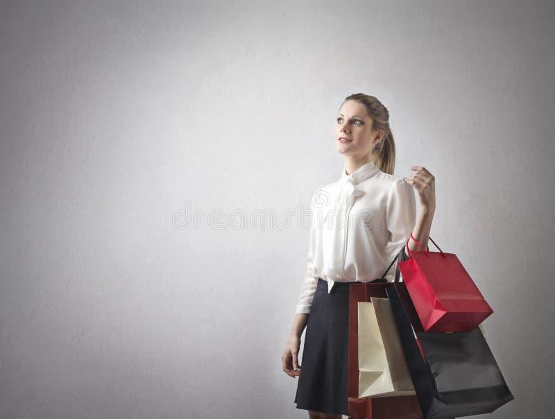 Donna con i lotti dei sacchetti della spesa fotografie stock libere da diritti