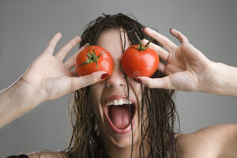 Donna con i pomodori sopra gli occhi. immagine stock