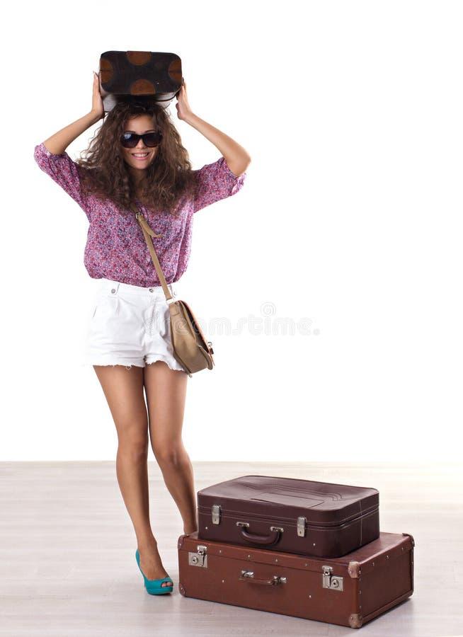 Donna con i riccioli scompigliati in occhiali da sole con i parecchi suitca fotografie stock