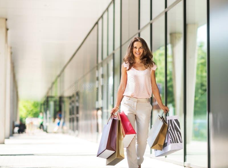 Donna con i sacchetti della spesa che cammina sul vicolo del centro commerciale fotografia stock libera da diritti